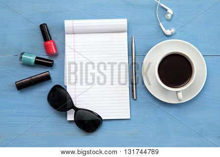 Sunglasses, coffee, to-do list on a blue table. Open notebook with white page.