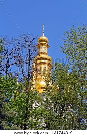 Bell tower of distant caves hidden in the spring foliage Kyiv-Pechersk Lavra Monastery in Kyiv, Ukraine