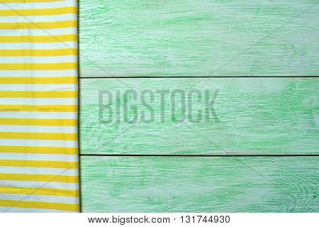 Tablecloth yellow textile on wooden green background
