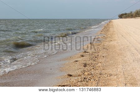 The waves of the Azov sea are rolled on a sandy shore