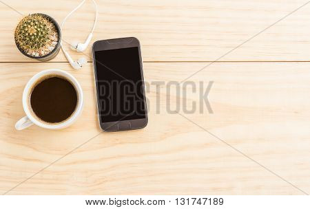 Coffee cup and smartphone on wooden table with copy space. top view