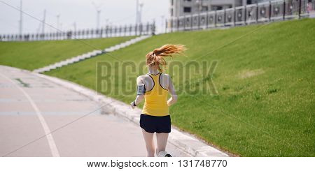 Young healthy lifestyle woman running at sunrise road. Girl running at asphalt road. Girl running in yellow sports shirt and black shorts