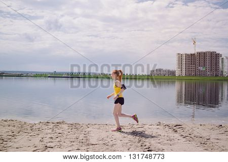 Young healthy lifestyle woman running at sunrise beach. Girl running at sand near water on city's beach. Girl running in yellow sports shirt and black shorts