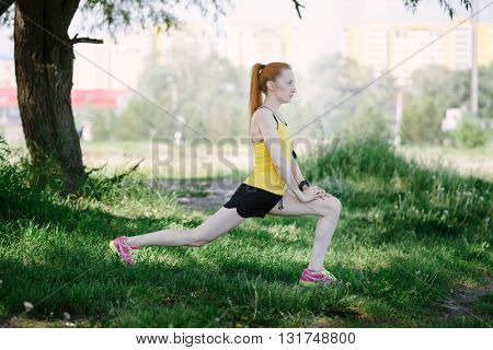 Young fitness woman runner stretching legs before run. Sportsman standing under tree.