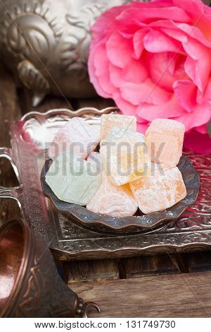 Lumps of Lokum or Turkish Delight in a tradition copper vase on oriental metal tray with pink rose