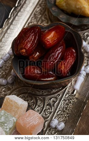 Date fruit with rosemary on metal oriental traditional tray