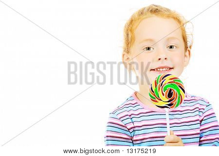 Portrait of a little red-haired girl licking lollipop. Isolated over white background.