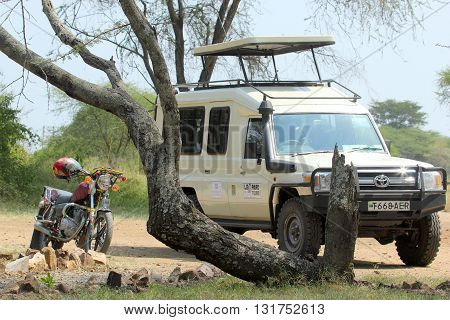 SERENGETI NATIONAL PARK TANZANIA - JUNE 11: jeep and motorcycle parked under a tree on June 11 2013 in Serengeti National Park. This famous and large area is visited by over 90000 tourists per year