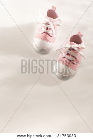 PAIR OF CUTE LITTLE BABY GIR'S SHOES ON WHITE BACKGROUND