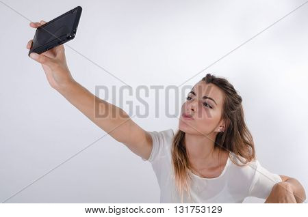 Young pretty girl making a selfie and sending a kiss