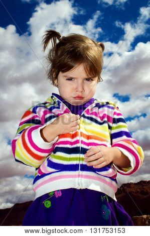 A very upset little girl stares down the camera against a blue and cloud filled sky. Her pouty face glare is rivaled by none.