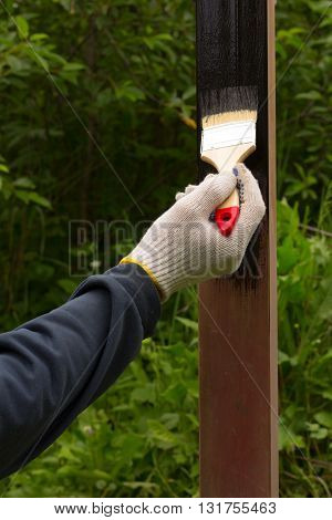 hand in glove rag paint brush brown steel pole in black on a background of green foliage