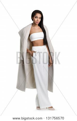 Fashionable African woman with long hair in white clothes standing on light background shove her hands in pockets and looking at camera