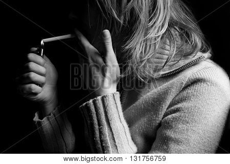 horizontal side view of a young blonde woman lighting a cigarette and smoking in the dark