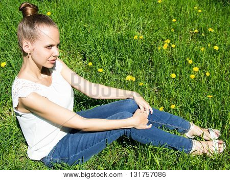 Beautiful girl sitting on the lawn with a yello dandelion