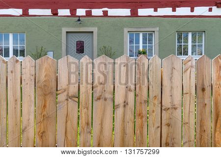 View to a garden fence made of wood with a house behind it