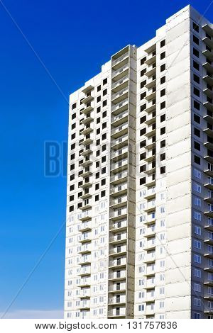 High-rise residental building under construction. On blue sky background