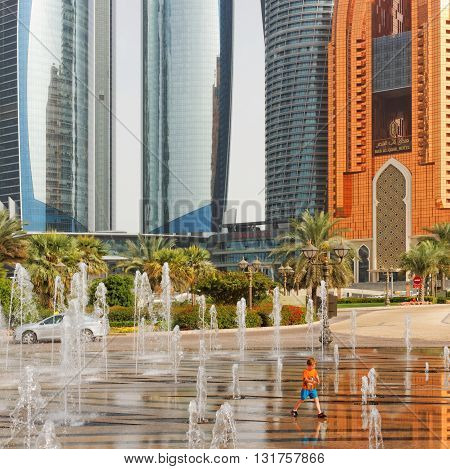 ABU DHABI CORNICHE, 30 MARCH 2016. Editorial Photograph of Small Boy Playing in Fountains in front of High Rise Buildings including Etihad Towers, the Regent Emirates Pearl and Bab Al Qasr Hotel