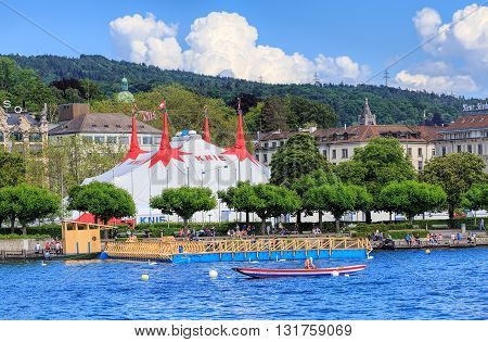 Zurich, Switzerland - 26 May, 2016: people on Lake Zurich with the tent of Circus Knie temporarily installed on Sechselautenplatz square in the background. Circus Knie is the largest circus of Switzerland, based in Rapperswil, founded in 1803.