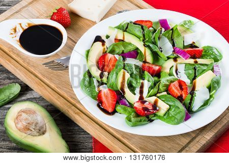 Strawberry baby spinach red onion goat cheese and avocado salad on a white dish on a cutting board with caramelized balsamic vinegar in a gravy boat top view close-up studio lights