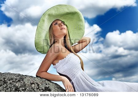 Beautiful young woman posing over summer sky.