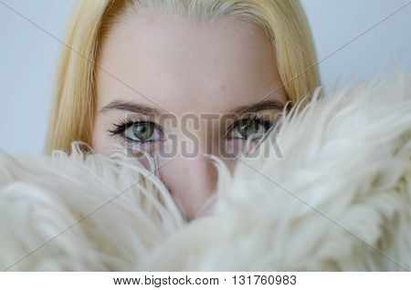 Young blonde woman with fur coat green eyes