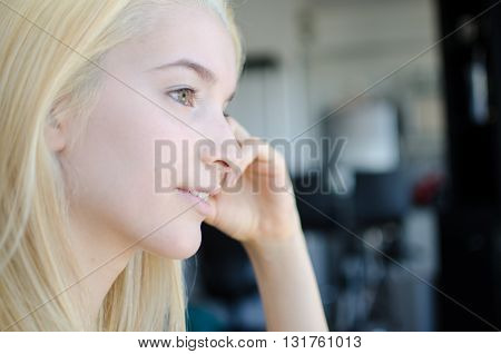 Young blonde woman portrait thoughtful smiling closeup