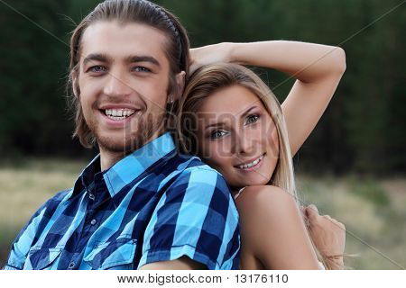 Beautiful young couple posing together outdoor.