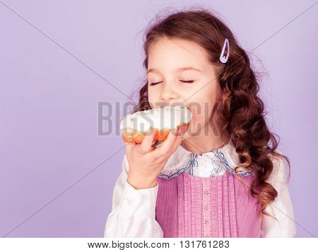 Smiling baby girl 4-5 year old eating donut in room. Childhood.