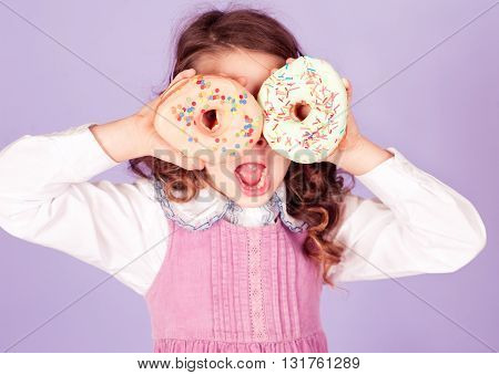 Cute kid girl 4-5 year old holding two tasty donuts in room. Having fun.