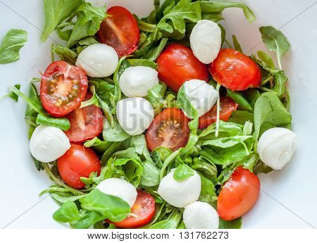 homemade caprese salad with cherry tomatoes and mozzarella cheese