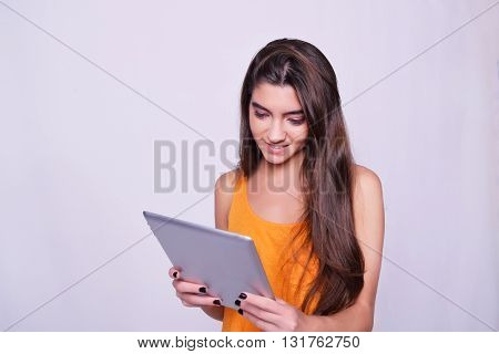 Tablet computer. Young woman holding tablet computer isolated on grey background. Casual caucasian beautiful woman.