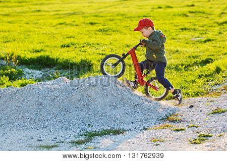 child on bike balance is drawn up on the mountain