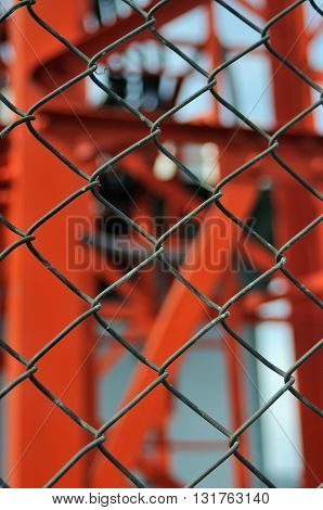Metal wire fence or cage on abstract blurry background (selective focus)