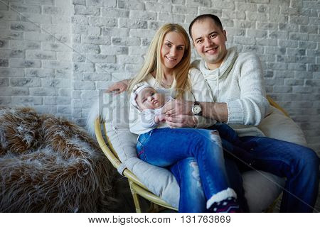 photo of happy father and mother with baby