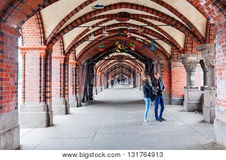 Berlin Germany - May 17 2016: Oberbaum Bridge with unidentified people. Its a double-deck bridge crossing the river Spree considered one of the citys landmarks. It links Friedrichshain n Kreuzberg