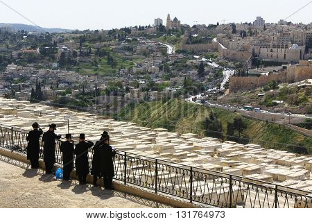 JERUSALEM, ISRAEL, 3 APRIL 2013. Editorial photo of Jewish Men Praying and Paying Respect at Jewish Cemetery on Mount of Olives in Jerusalem, Israel