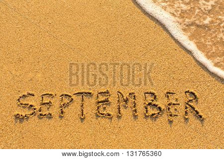 September - inscription on sand beach with the soft wave.