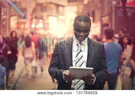 Happy businessman checking his tablet