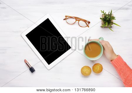 Top view of tablet gadget with copyspace lipstick and a cup of coffee with muffins on a white wooden table. Home office concept. Businesswoman concept.
