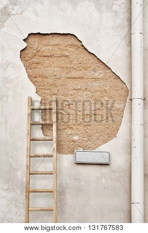 cracked wall with street sign, ladder and rain water pipe