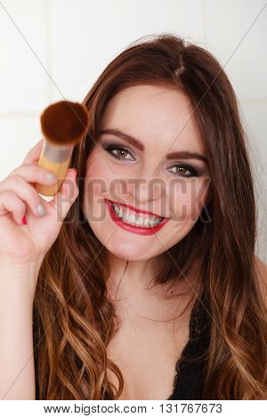 Smiling girl making makeup in bathroom. Woman take care about look.