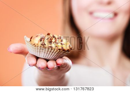 Delicious tasty sweet cake cupcake in human hand. Gluttony concept.