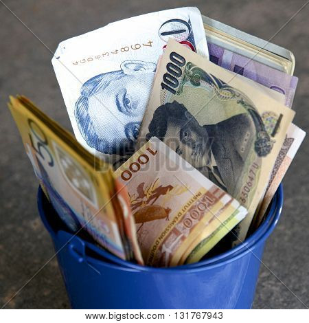 Bucket full of cash with a range of currencies.