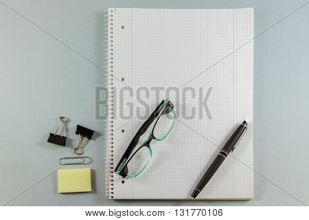 Notebook With Blank Paper, Color Sticky Notes, Pen, Glasses And Clips On A  Grey Background