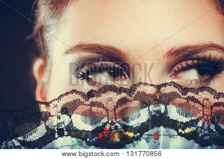 Beauty of women. Young attractive woman with strong dark make up. Portrait of elegant lady with fan close to her face on black background.