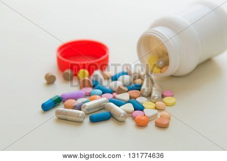 Close up of various medicine pills on white table.