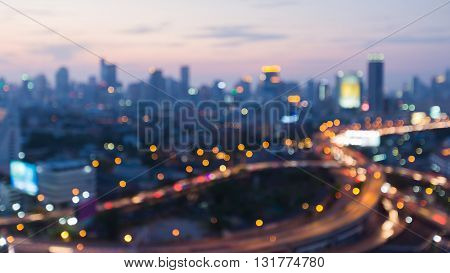 Blurred interchanged road and city downtown background after sunset, abstract background