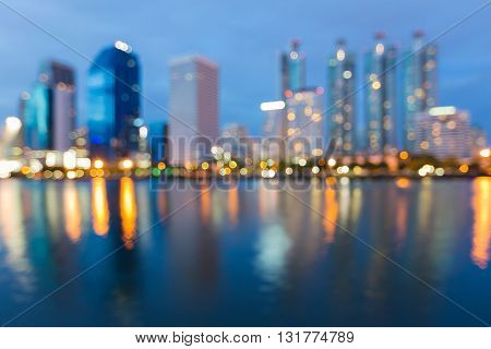 Blurred office building lights waterfront night view, abstract background