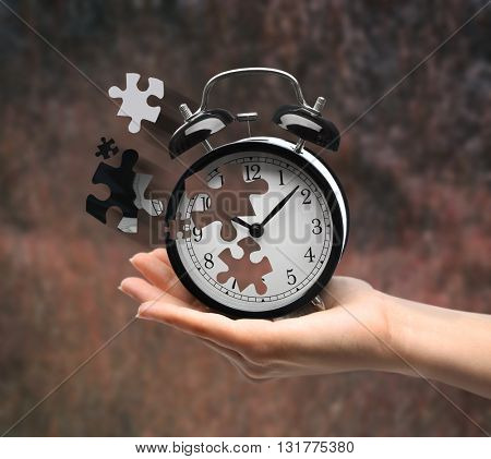 A retro alarm-clock on female hand on dark blurred background. Lost time concept